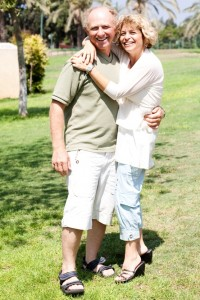Affectionate senior couple embracing in the park and posing in front of camera